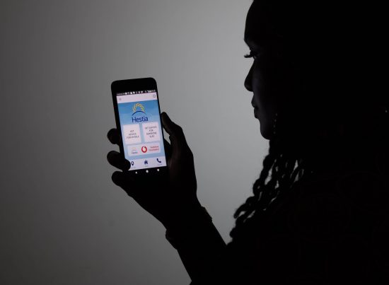 A woman holds up a smartphone showing the welcome screen for Bright Sky, an app created by the Vodafone Foundation in partnership with Hestia