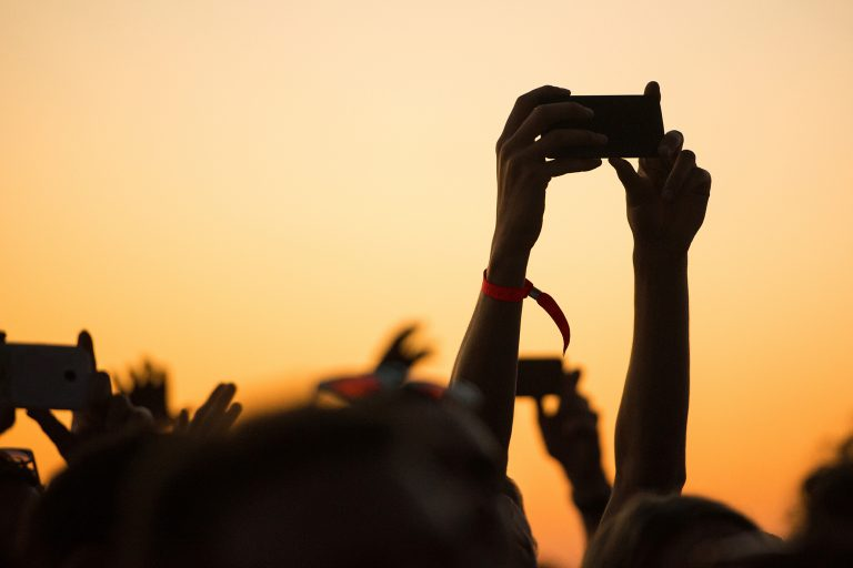 Sunset image showing people's hands in the air, filming and taking photos