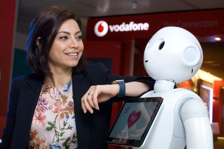 Photo of Vodafone UK's Samira Maleki, Operational Governance & Transformation Manager, pictured with Pepper the humanoid robot in front of a Vodafone store