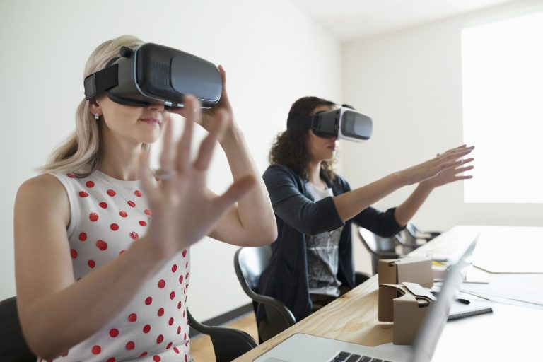 Photo of two women using VR headsets in the office
