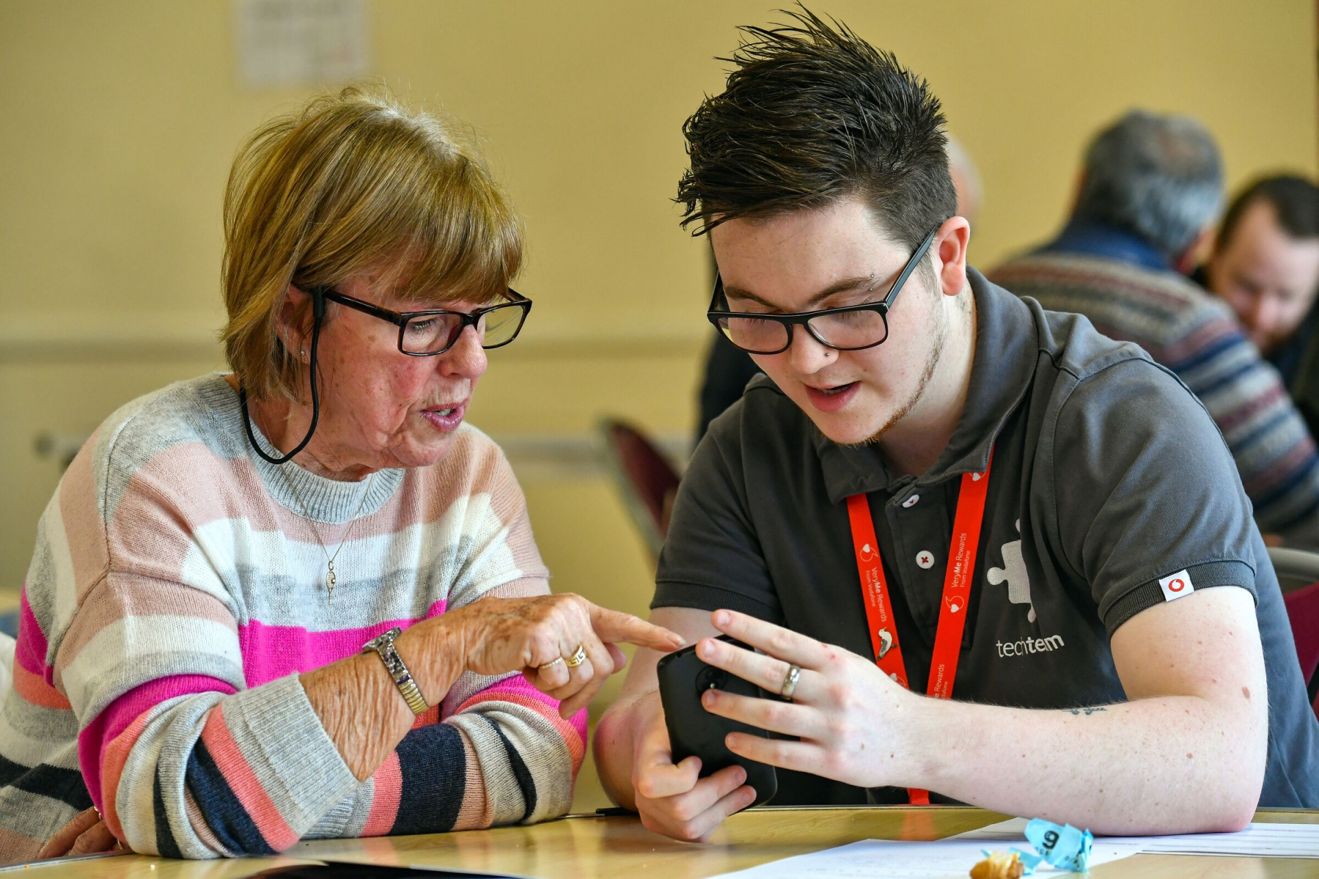 Photo of a Vodafone Tech Expert helping a woman with her tech questions at a TechConnect event in Carnival Hall, Basingstoke, 26.02.19