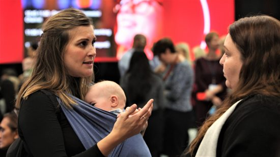Woman with baby discusses returning to work with a Vodafone helper