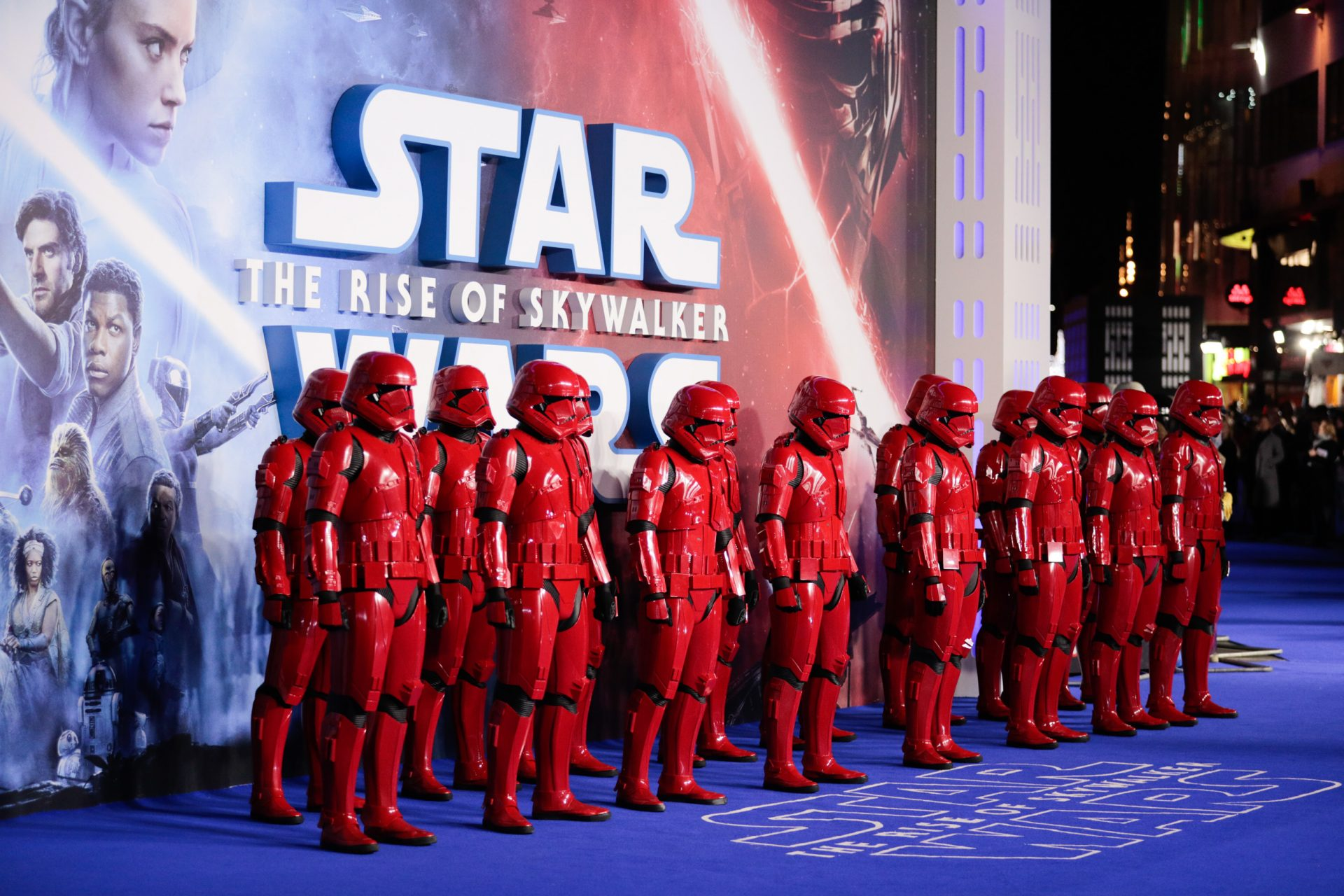 Stormtroopers in red uniforms lined up against Star Wars: The Rise of Skywalker poster