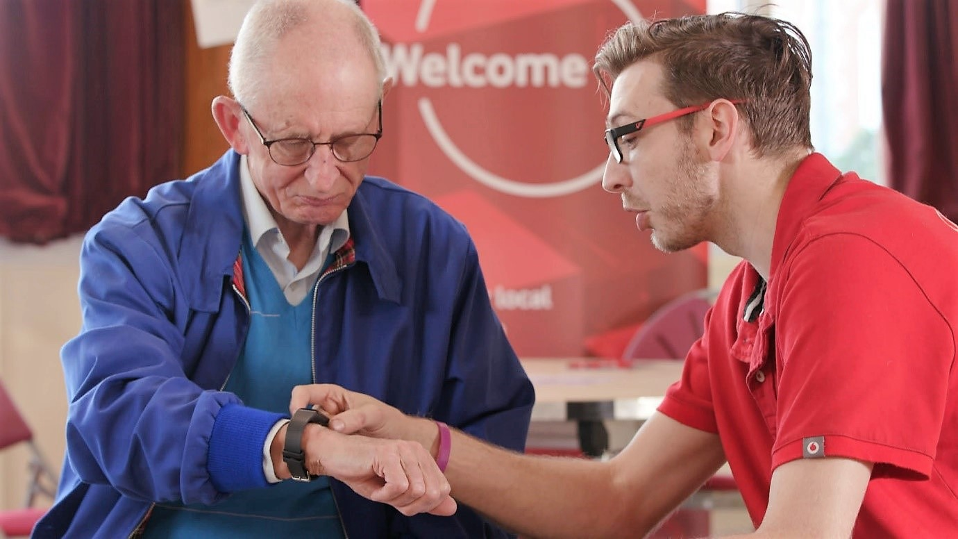 Vodafone tech expert shows elderly man how to use a smart watch
