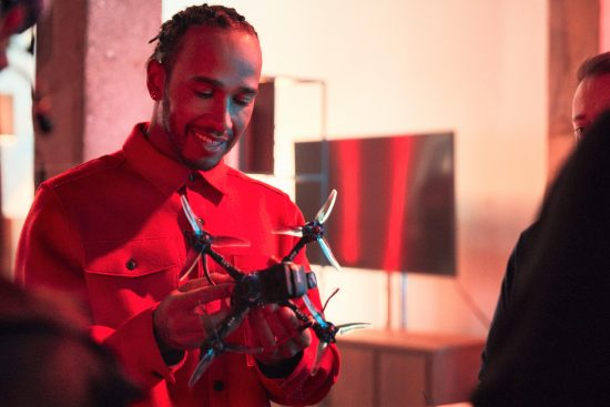 Lewis Hamilton smiling while inspecting a racing drone