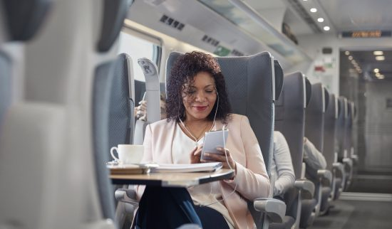 photo of a businesswoman using a smartphone on a passenger train