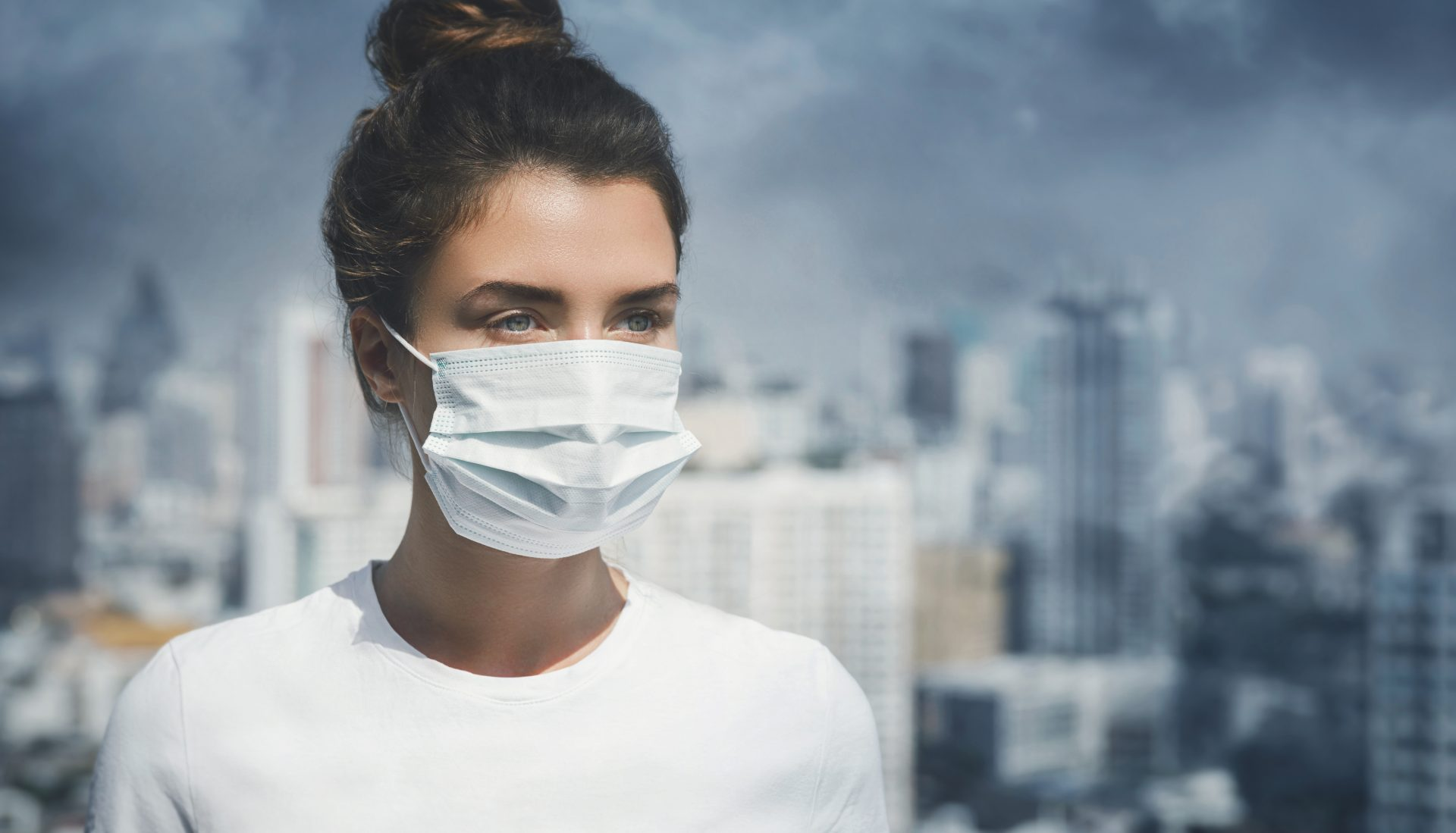 Young woman wearing face mask in polluted cityscape