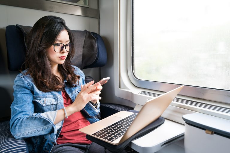 Young woman on train with open laptop looking at smartphone