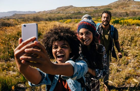 Friends hiking in the countryside and taking a selfie