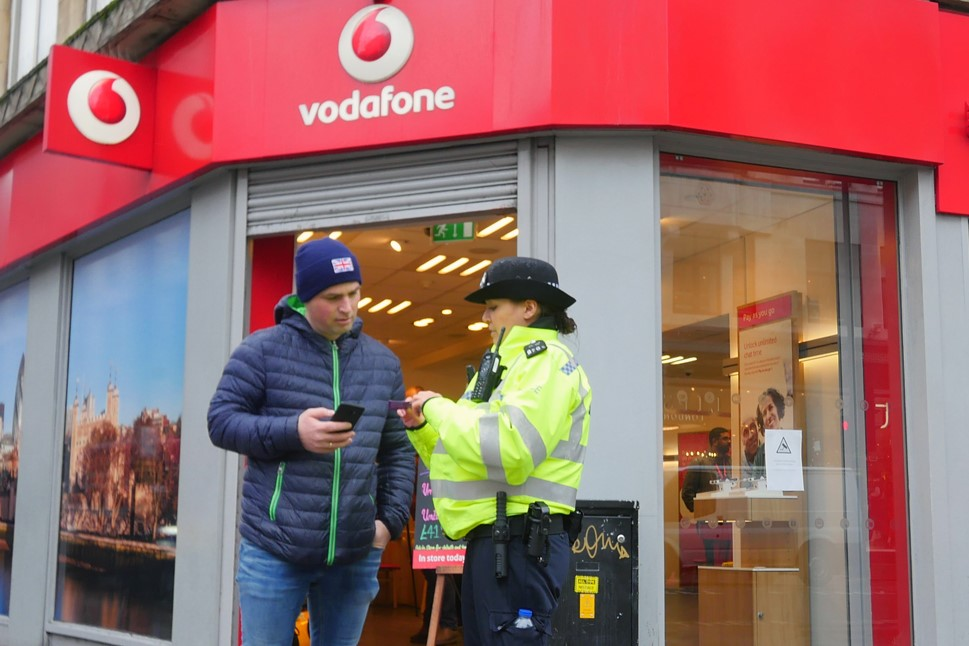 Police officer talking to member of the public outside Vodafone's Oxford Street store