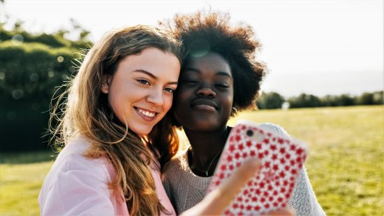 Photo of two girls taking a selfie in a field using a smartphone