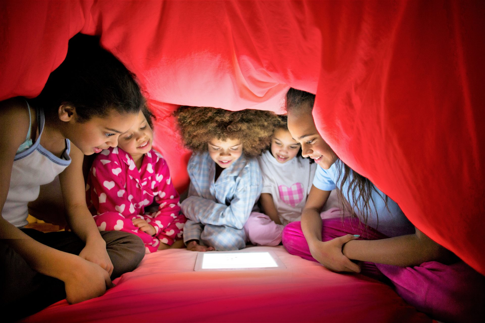photo of children using their tablet underneath a blanket tent