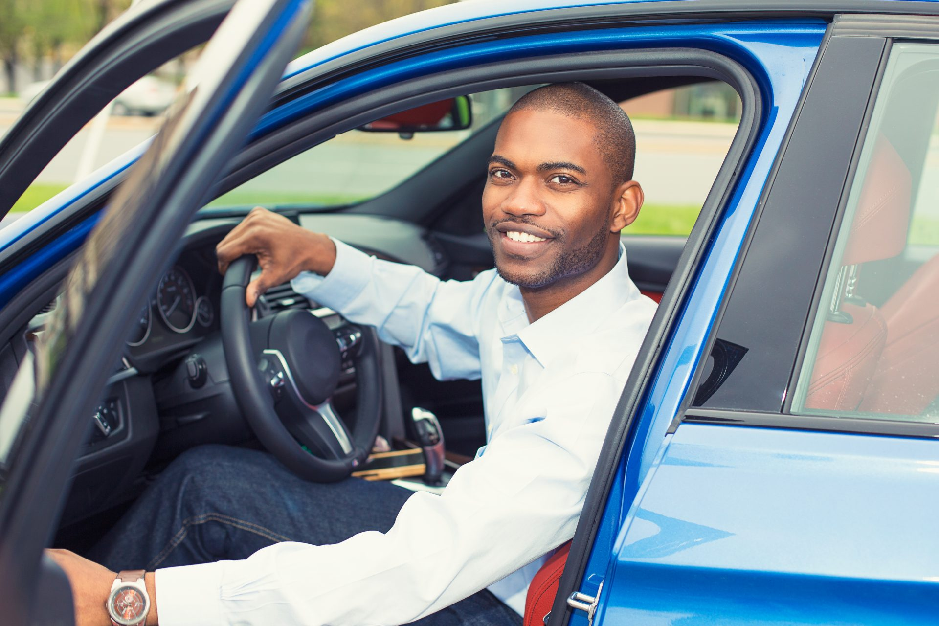 Young smiling man sitting in new car