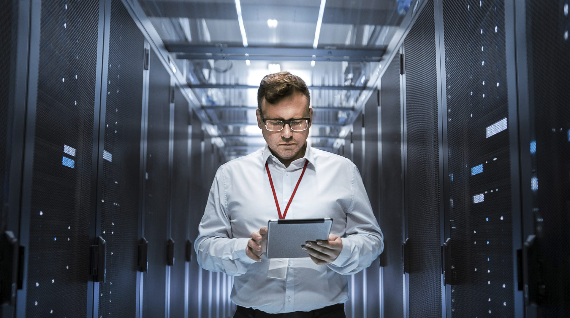 IT Technician Walks Through Rows of Server Racks in Data Centre. Simultaneously He Works on a Tablet Computer.