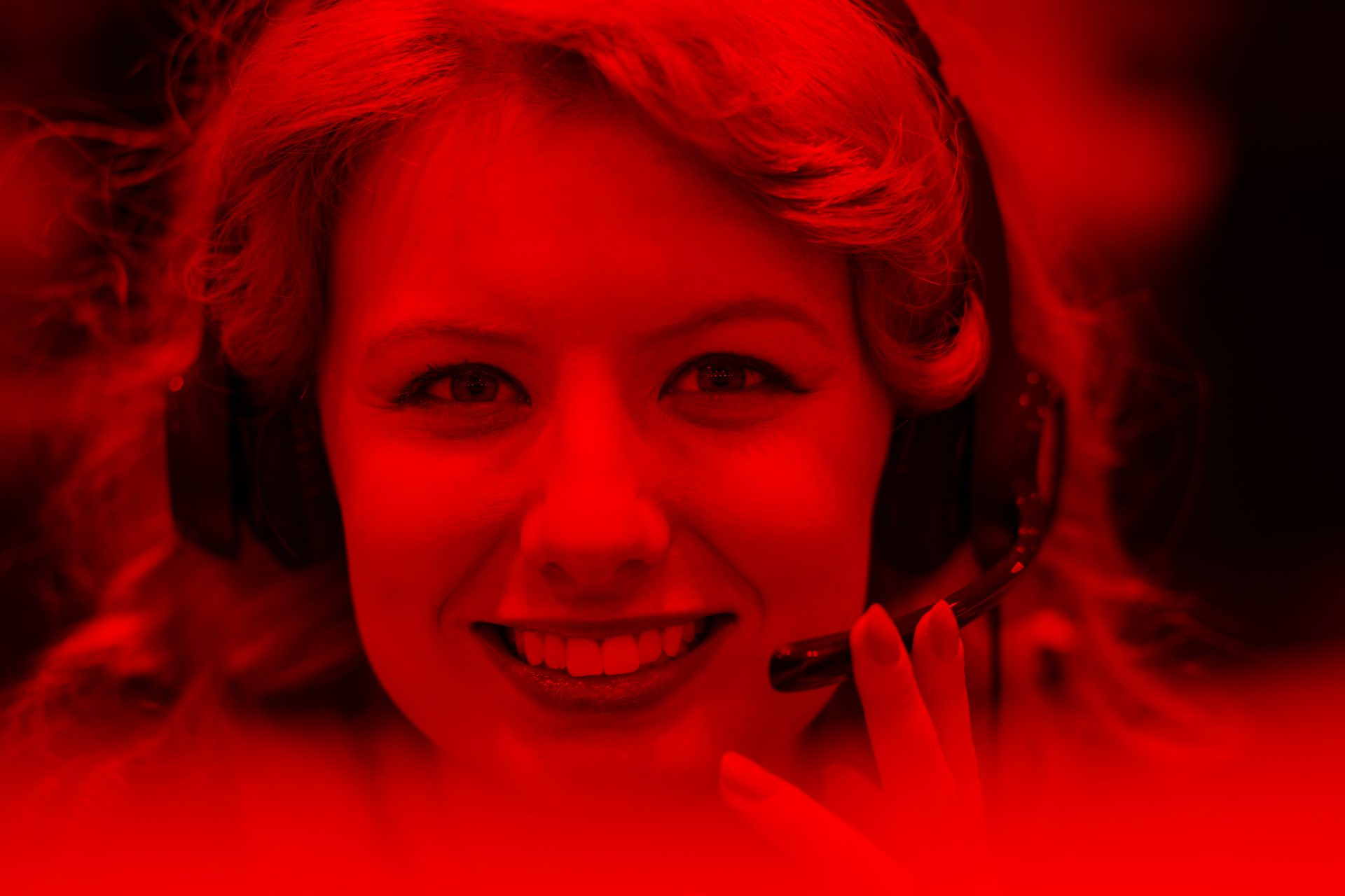 Smiling woman on call centre headset with red filter