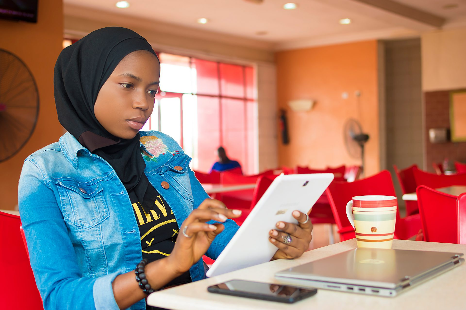 Nigerian muslim girl accessing tablet computer
