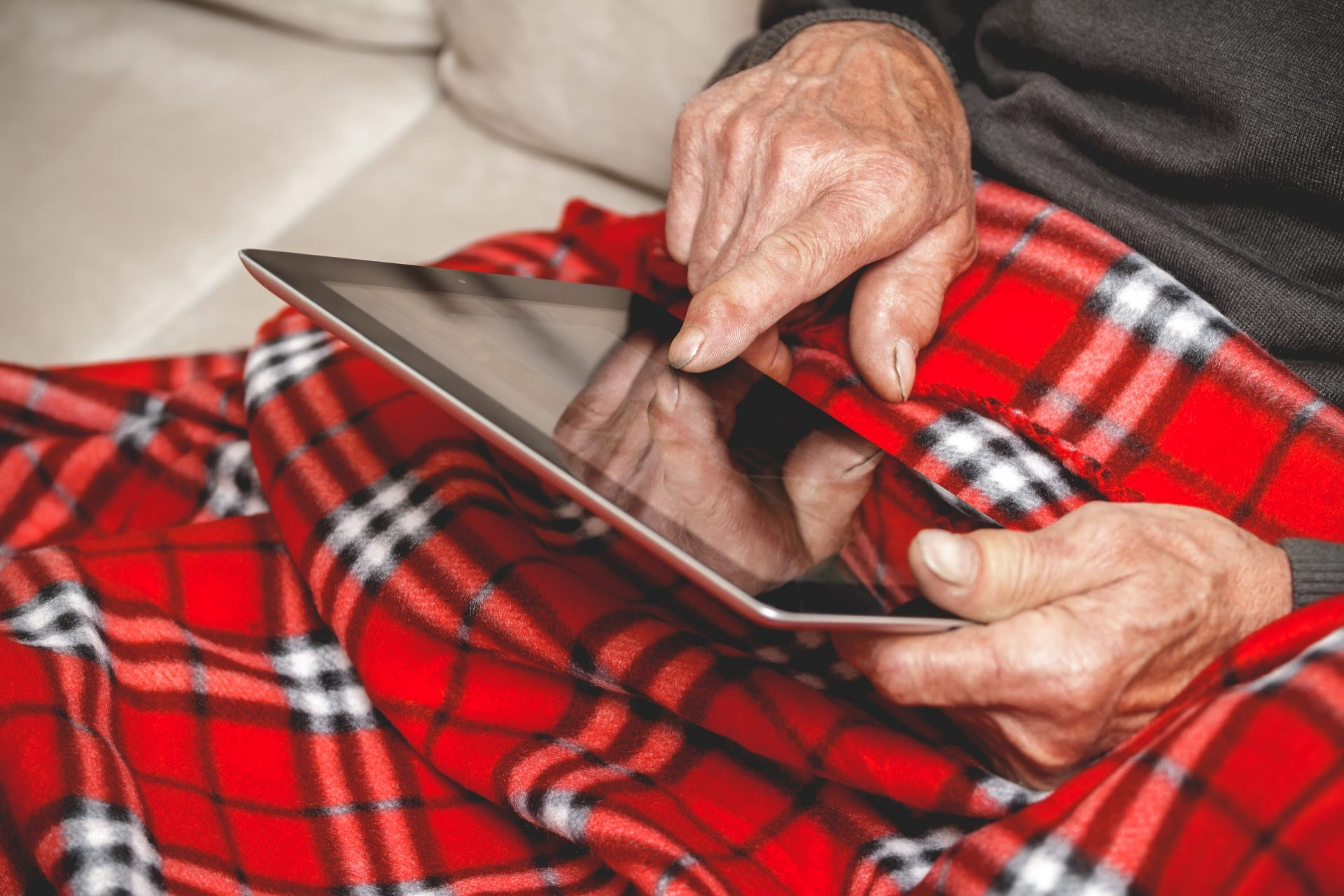 Elderly man sitting on sofa reading tablet computer