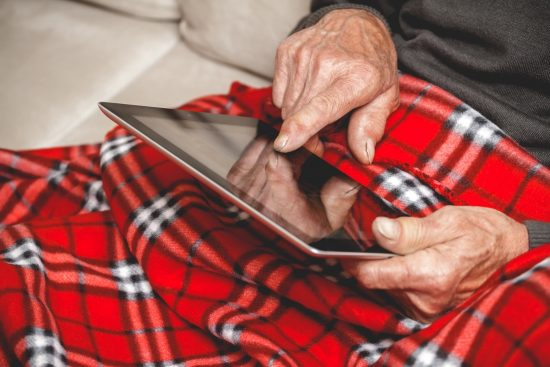 Elderly man sitting on sofa reading tablet computer