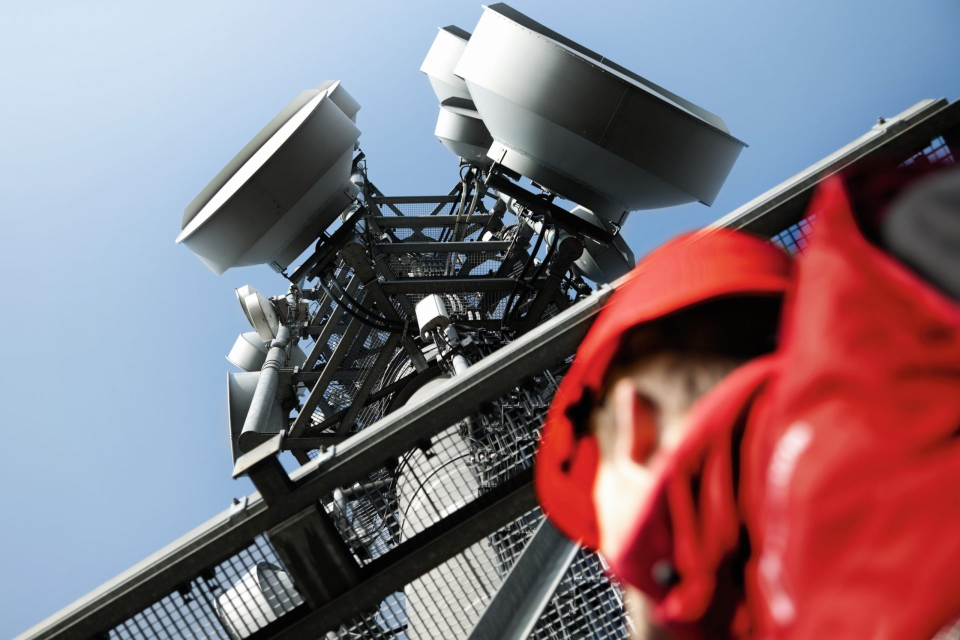 photo of a Vodafone engineer looking up at a Vodafone network mast