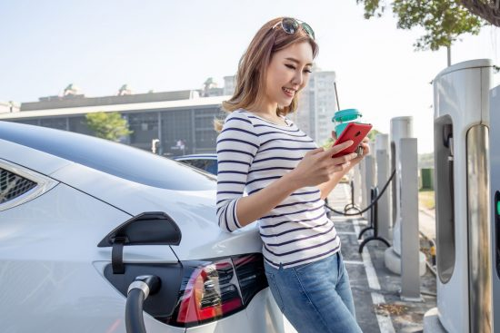 Young woman looking at smartphone while charging her electric car