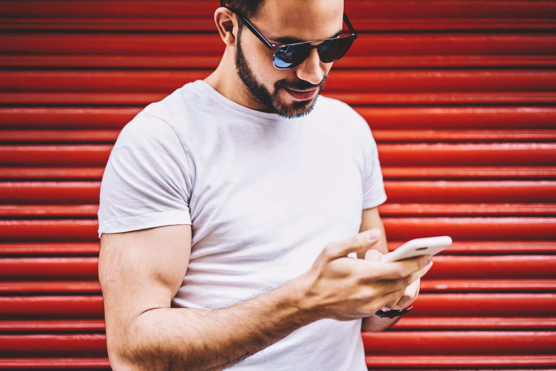 Young man in sunglasses looking at smartphone against red background