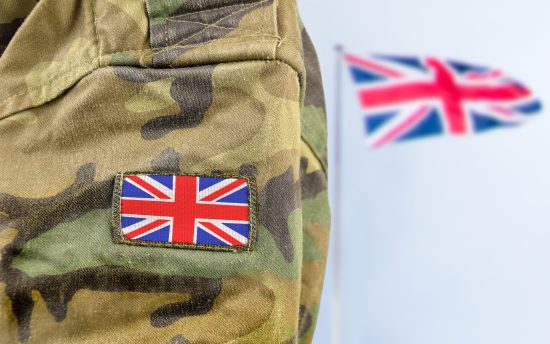 Miltary person standing in front of Union Jack flag