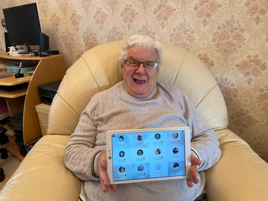 Elderly man holding Alcove Video Carephone