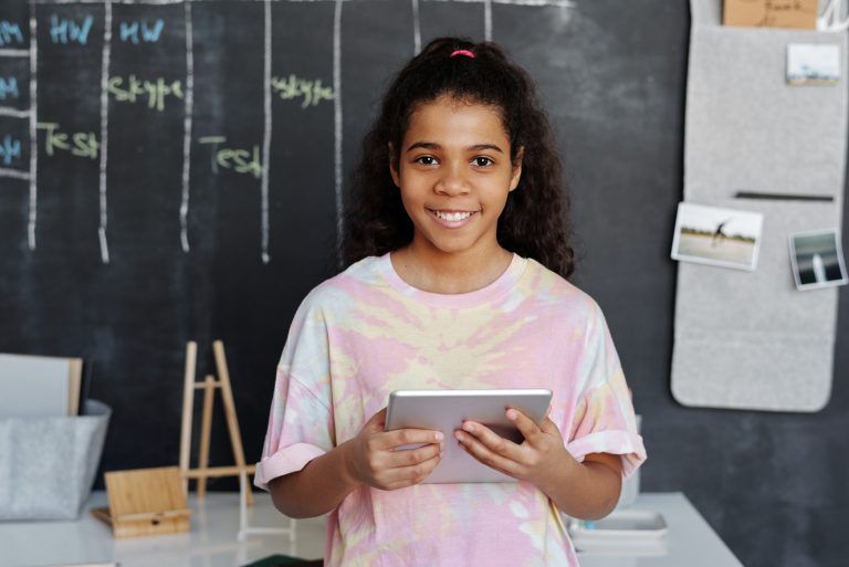 Smiling girl holding tablet in classroom