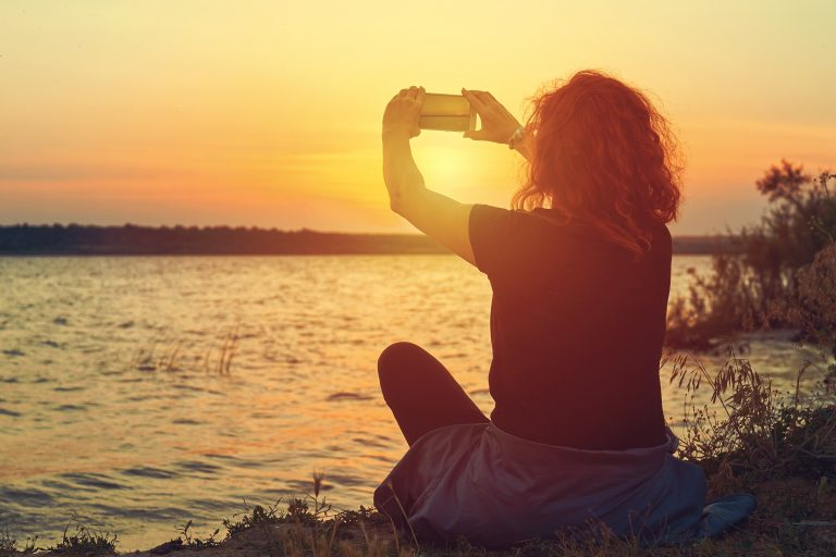 Woman sitting next to water taking photo of sunset