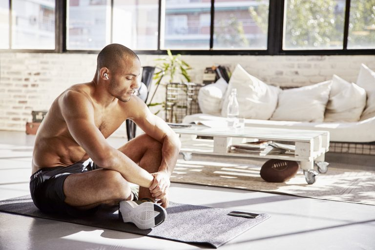 Athletic man sitting crosslegged on floor listening to smartphone