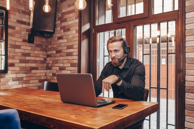 Man with headset video calling on laptop