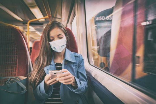 Young woman on train wearing mask and looking at smartphone