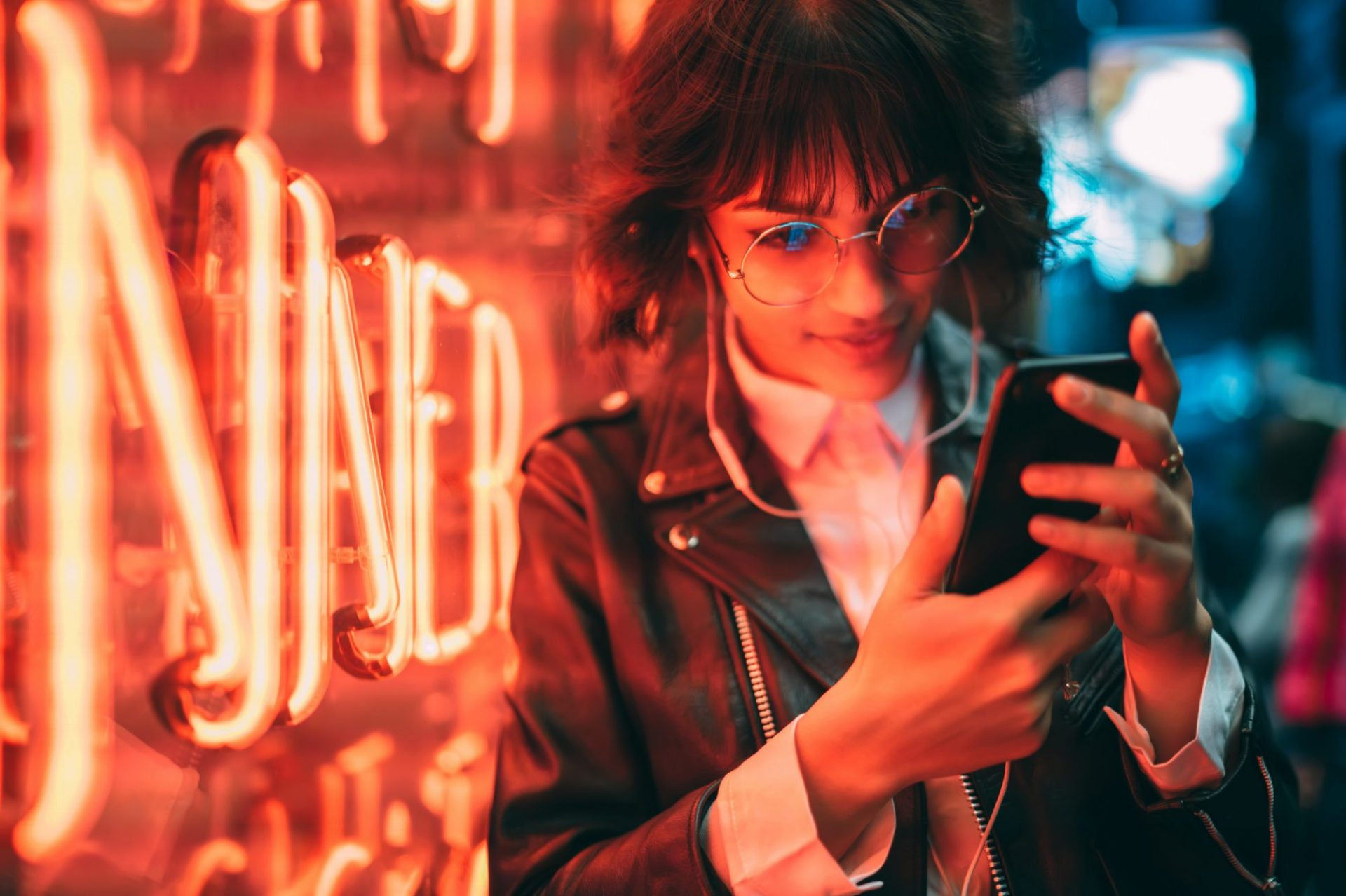 Young woman looking at smartphone next to red neon light