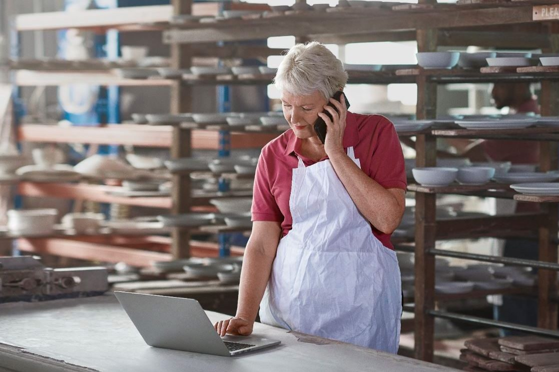 Small business owner on phone looking at laptop