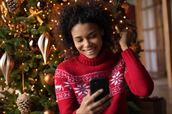 Young woman in red Christmas jumper smiling at smartphone