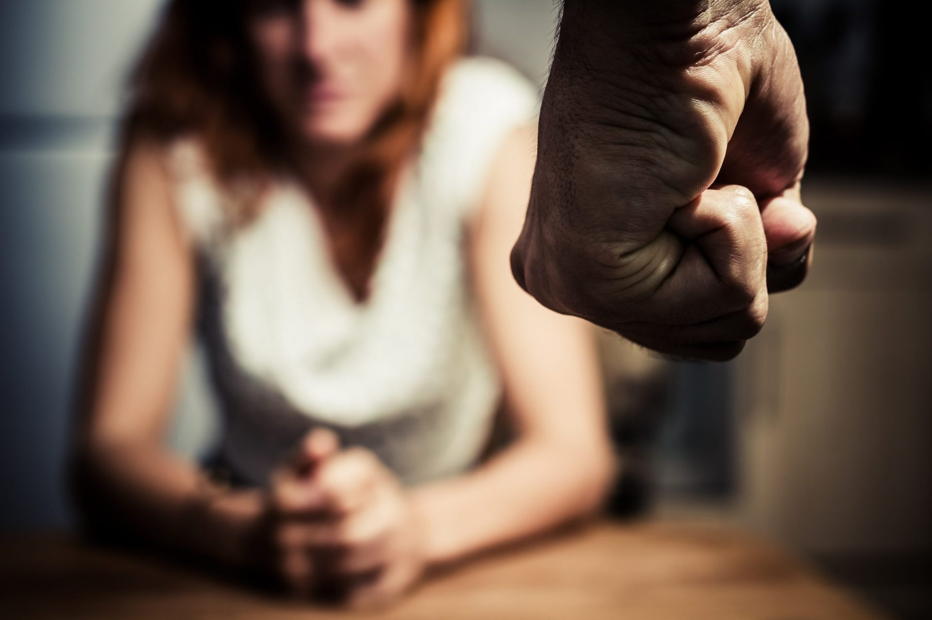 Domestic abuse: man with clenched fist, sitting woman in background
