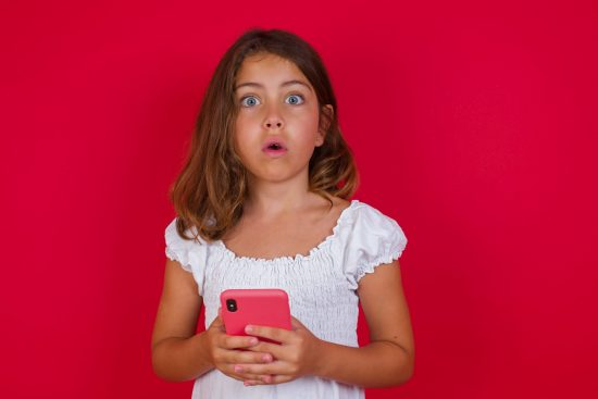 Young girl surprised by what she's seen on her smartphone