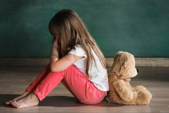 Young girl sitting with teddy bear