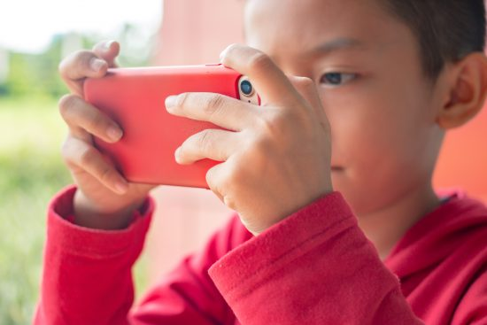 Young boy playing with smartphone