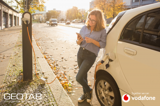 Woman charging electric car while looking at her phone