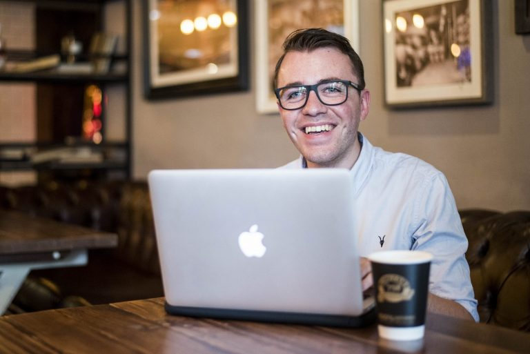 Tech expert Harvey Morton sitting at cafe table in front of laptop