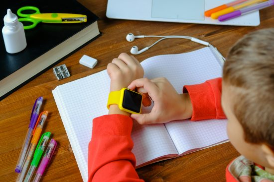 Young boy wearing smartwatch at desk