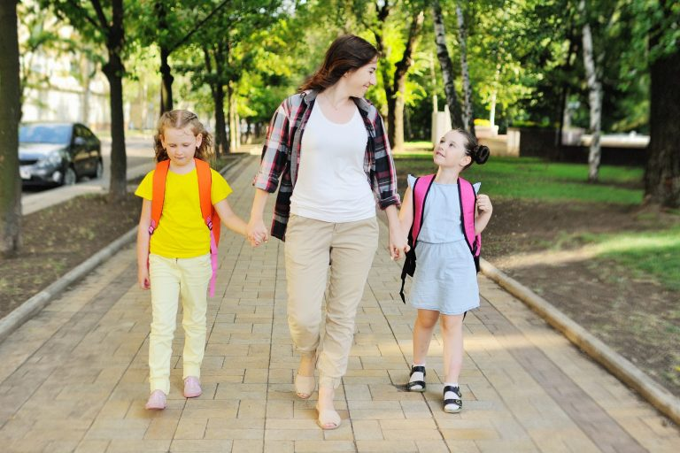 Mother walking young girsl to school