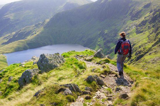 Female hiker walking in mountain scenery