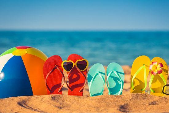 Beach ball and flip flops on a beach