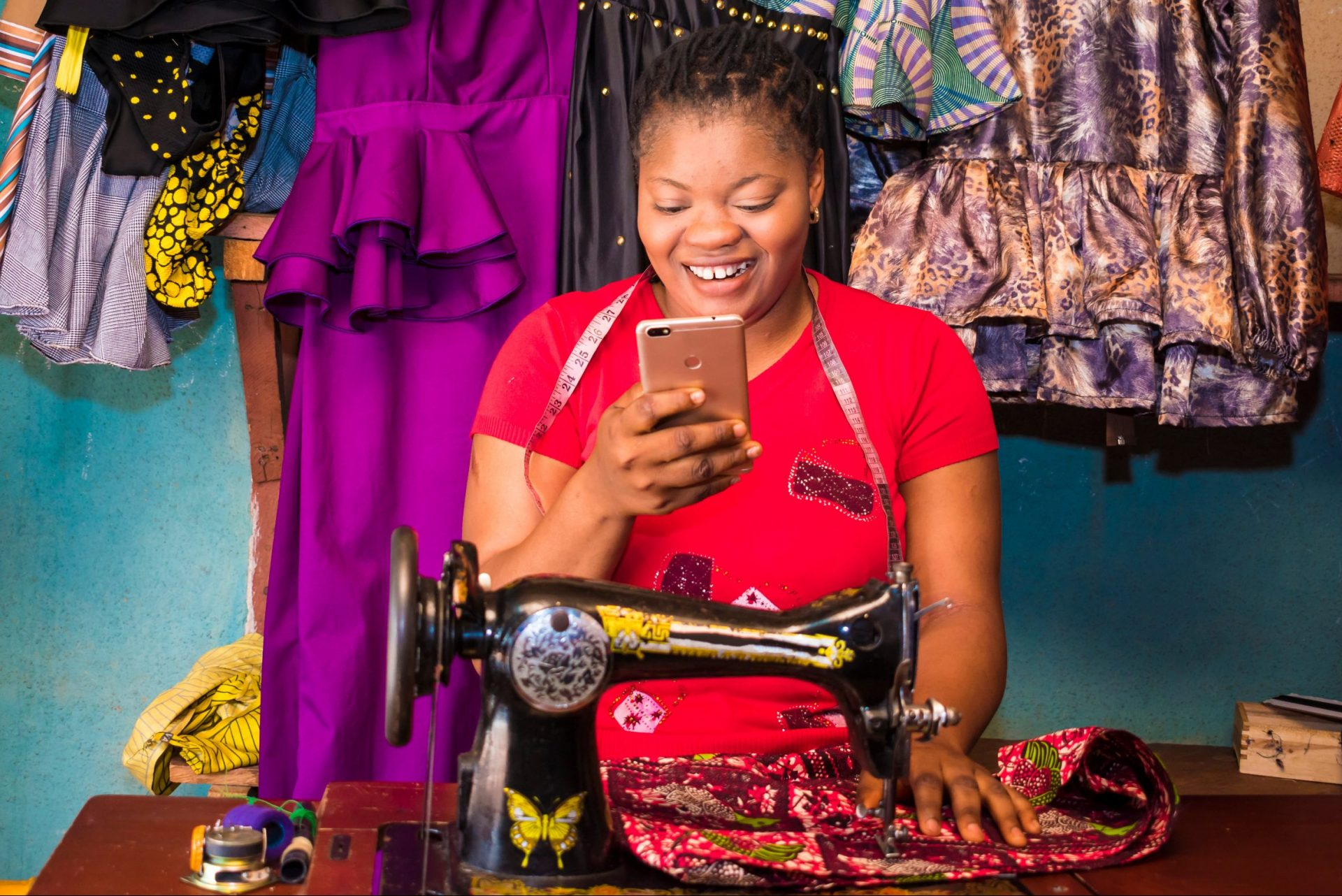 Sole trader tailor looking at smartphone
