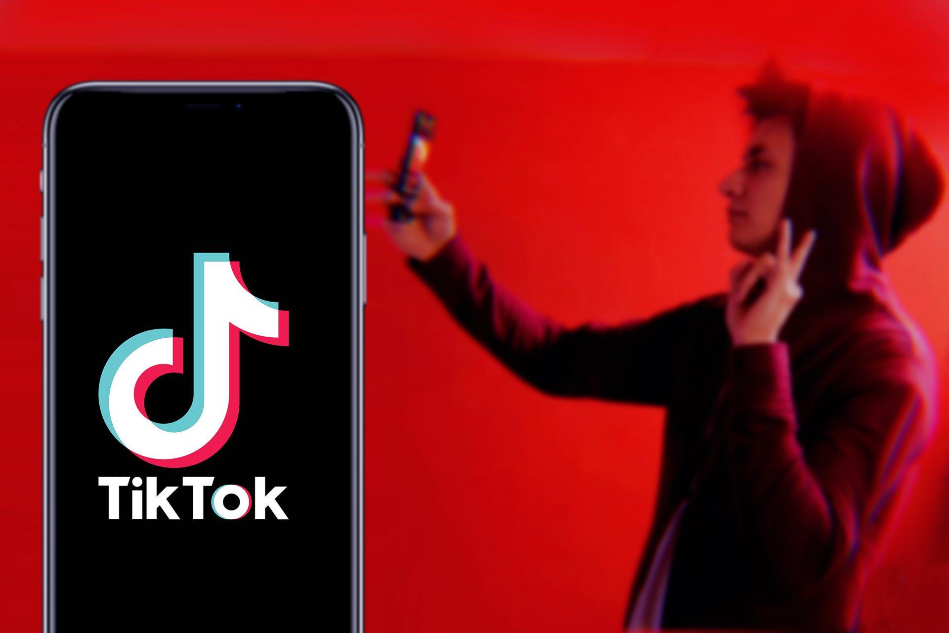 TikTok logo and boy taking selfie on red backround
