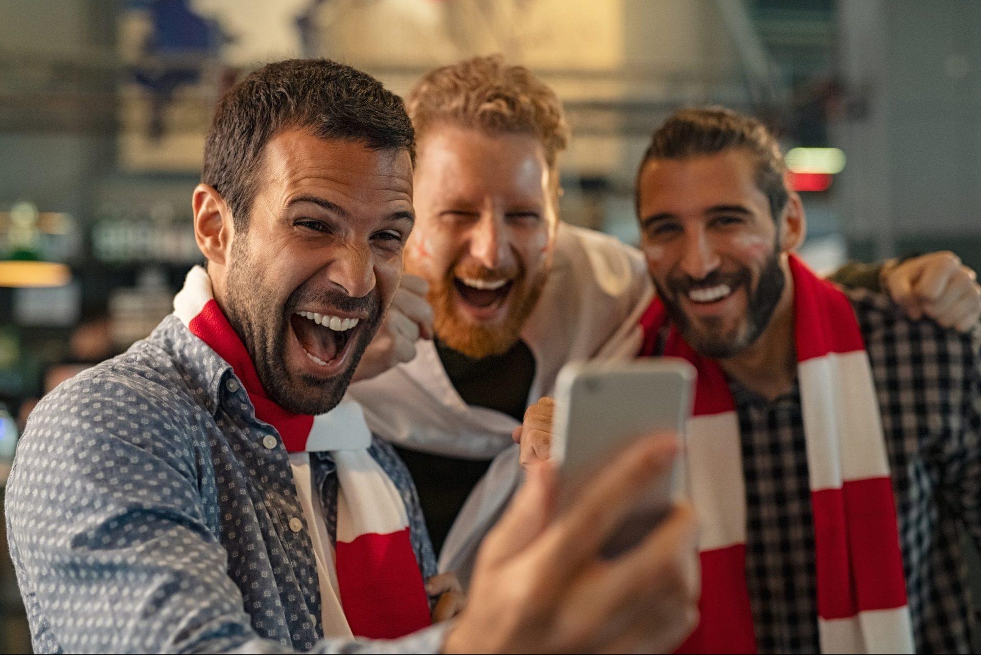 Football fans watching match on smartphone