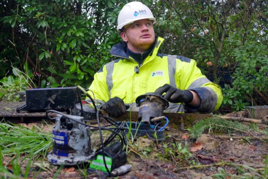 photo of an SES Water engineer attending to an IoT sensor