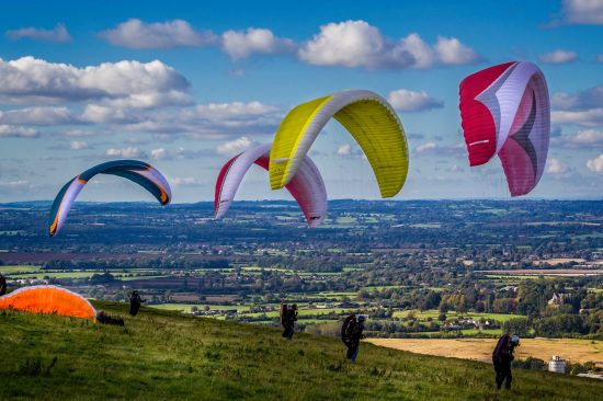 Four paragliders on UK hillside ready for take-off